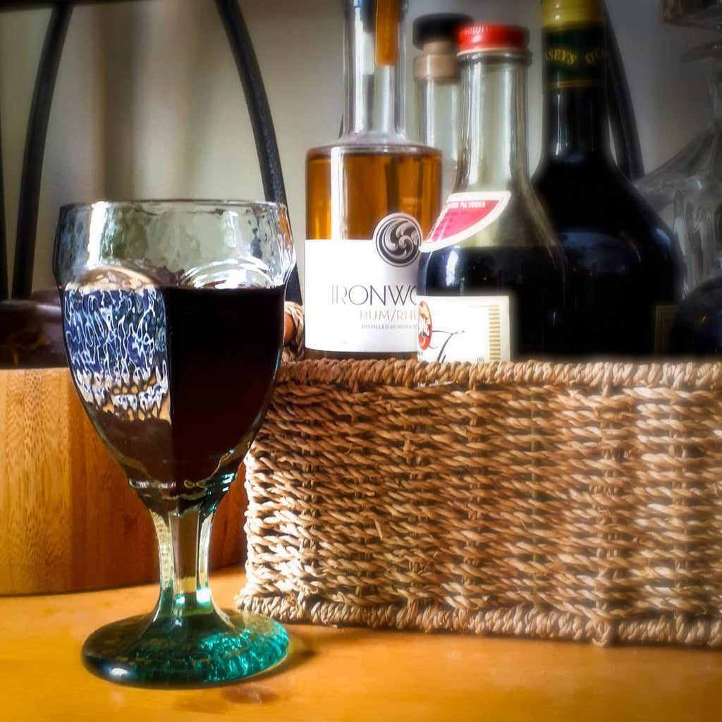 glass of wine and bottles in basket