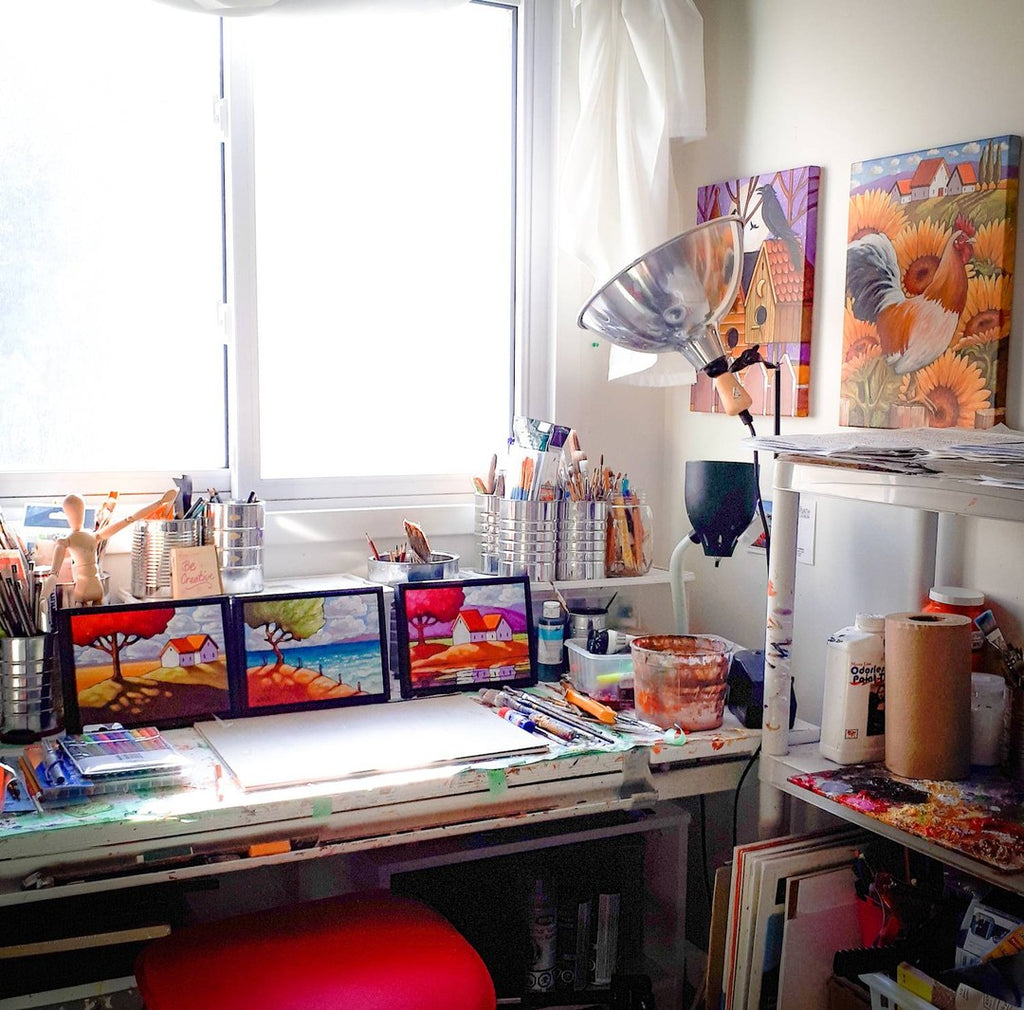 studio art table with paintings