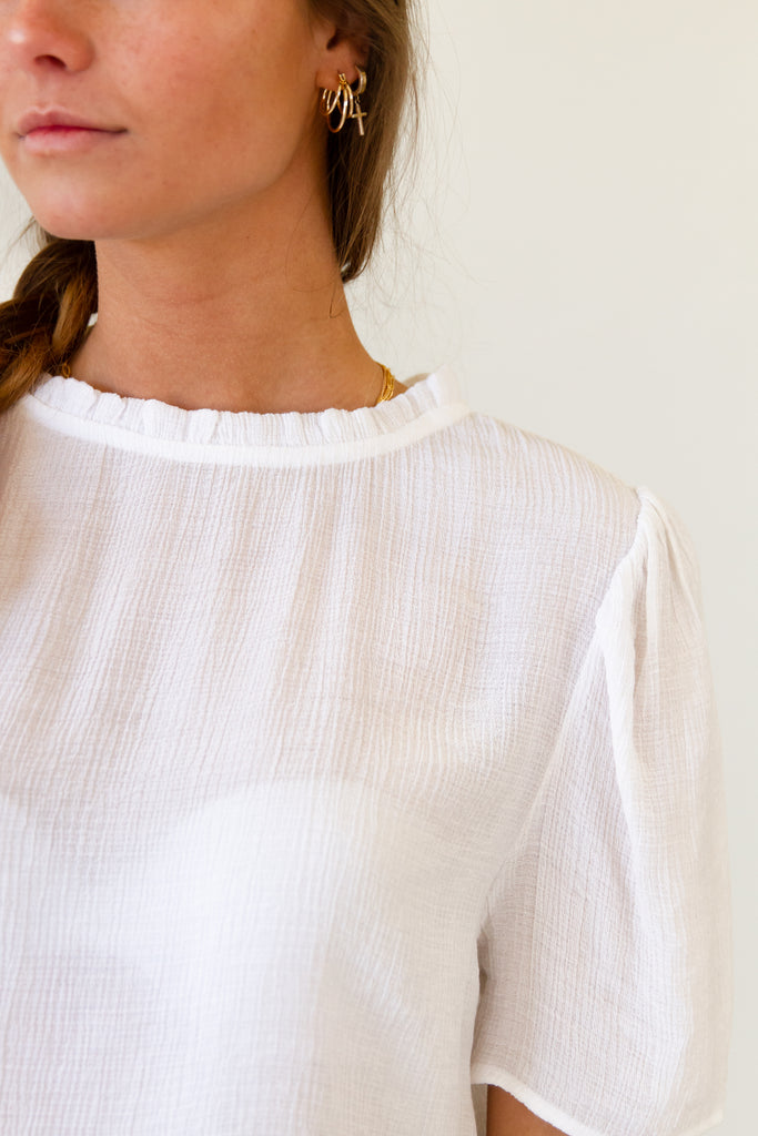 white sheer smocked high ruffle neckline short sleeve top