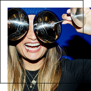 Girl holding two Crispy Gatsby Shine stainless steel glasses up in front of her eyes and laughing