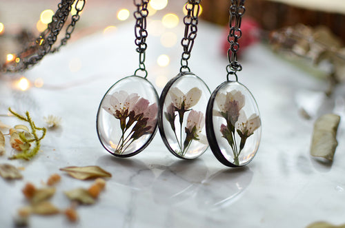 A pendant featuring cherry blossoms preserved in glass (stained glass technique, black patina).