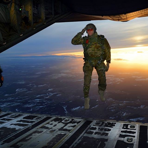 A US soldier salutes his fellow soldiers while testing Night Vision equipped Levitation Boots outside of a C-130 Hercules aircraft over a drop zone in Germany.