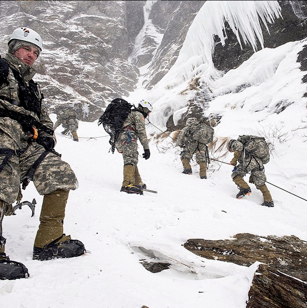 "US soldiers take an opportunity to test boot warmth during their climb of Smugglers' Notch in Jeffersonville, Vt, while looking for a frisbee that went wide during a game of ""ultimate""."