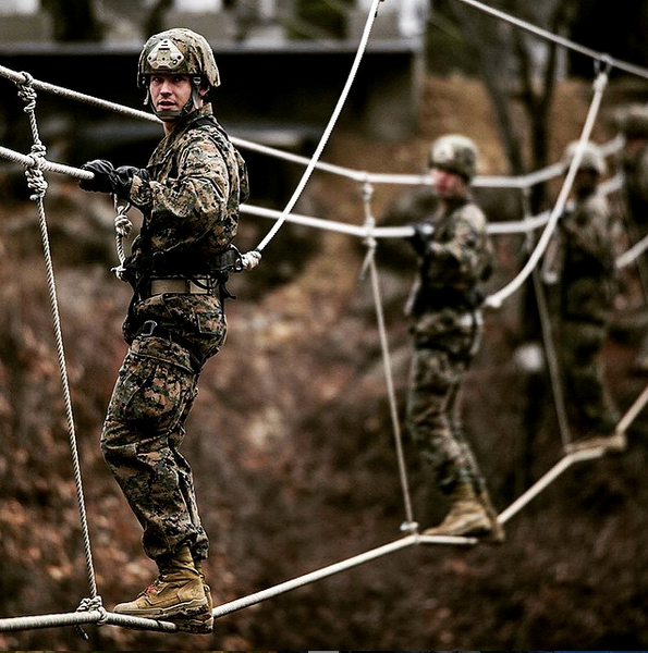 A US Marine assigned to the 5th Air Naval Gunfire Liaison Company, 3rd Marine Expeditionary Force Headquarters Group, during boot sole testing on rope bridges.
