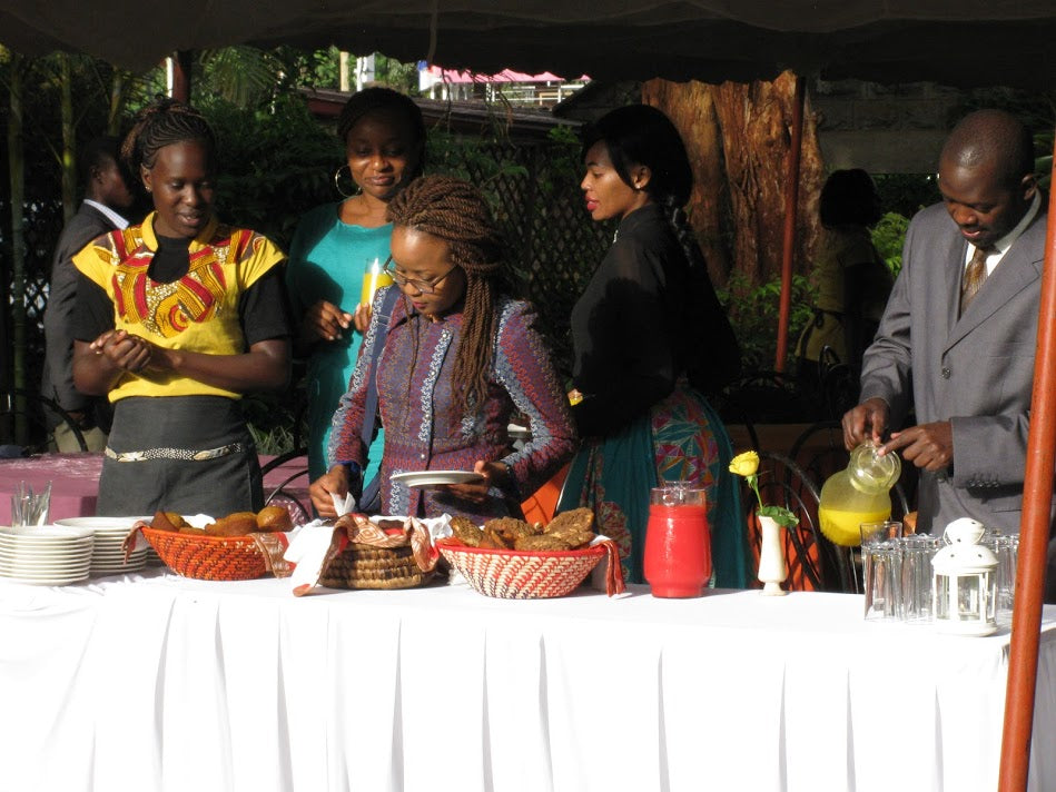women by the food table at amani kenya during white ribbon event