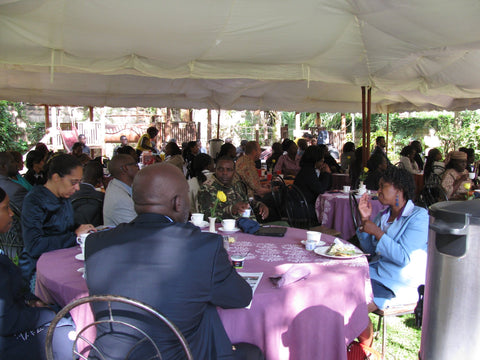 people gathered and eating at amani kenya for white ribbon event