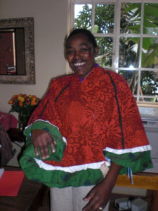 Joyce doesn't mind having a little fun at work...here she is wearing a Christmas tree skirt as a poncho!