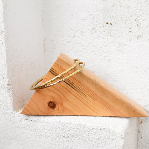 Brass Bangles, handmade bracelet from artisans in kenya, displayed on a wood triangle.