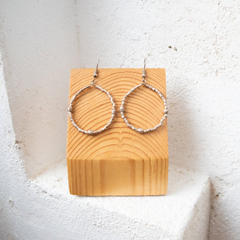 African beaded hoop earrings on a wooden block against a white wall