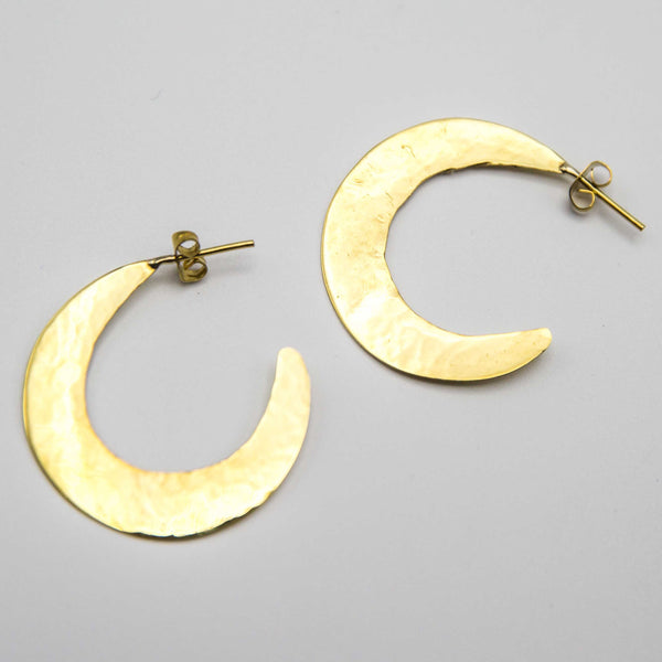 Crescent shaped earrings made from hammered brass on a white surface.