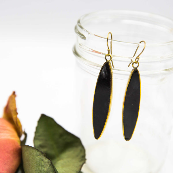 Natural brass and wood earrings displayed on a mason jar.