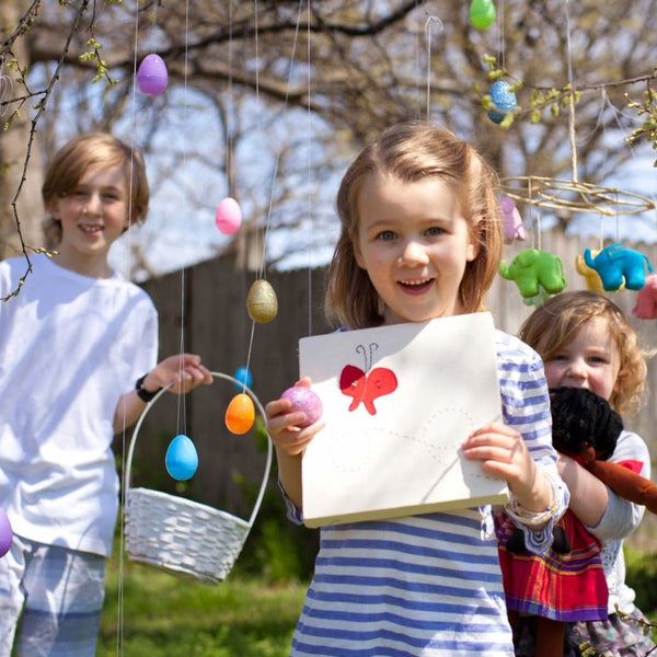 Kids playing while girl holds up her butterfly Framed Animal Wall Hanging at easter
