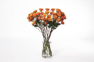 Orange peach spray roses in their vase. Orange and peach spray roses signify passion and energy.