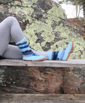Crocheted slipper-boots covering the leg to mid calf, in blues ranging from a light pastel blue to denim blue, to bright ocean blue. Handmade in Canada.