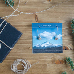 Dainty hand-stamped earrings featuring the state of Alaska. Displayed on a photograph  of the Alaskan mountains