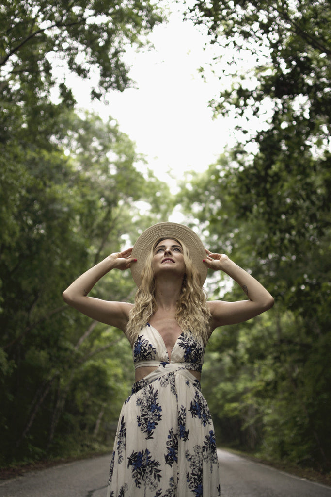 Alyssa standing in the middle of a large road in the forest wearing a long white and blue maxi dress
