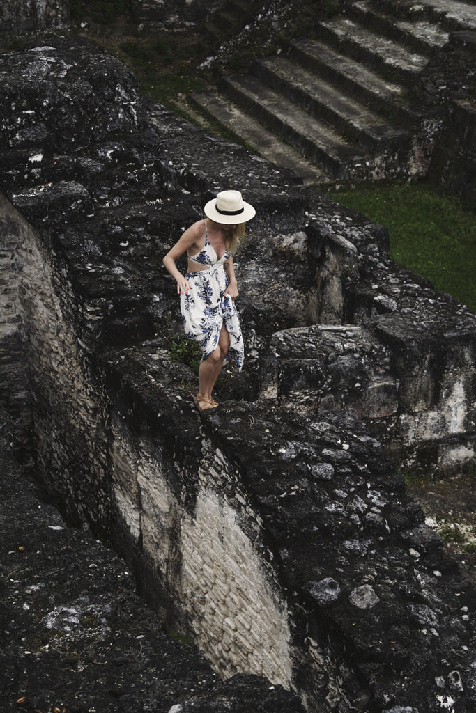 Alyssa standing on some of the ruins in Tikal National Park and exploring them as she is wearing a long white and blue maxi dress