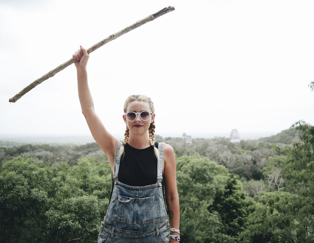 Alyssa is holding a large stick at the top of a monument and wearing overalls, a black tank top, and boxer braids