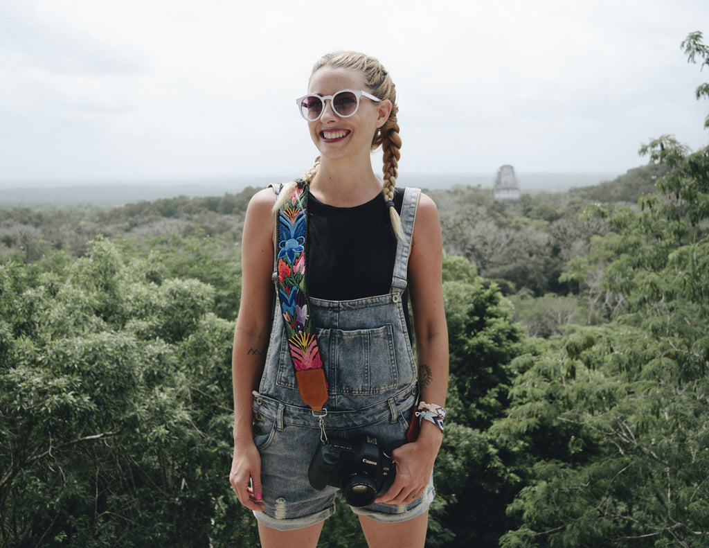 Alyssa is holding the camera with the camera strap at the top of a monument and wearing overalls, a black tank top, and boxer braids