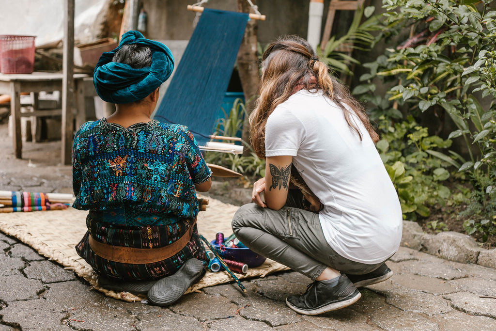 Hiptipico long-term artisan partner Teresa instructing tour participant to weave, ethical weaving tours, artisan home visits, Guatemala artisan visit