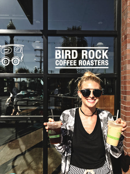 Fashion and lifestyle blogger, and Hiptipico founder Alyssaya poses in front of a coffee shop holding two coffee cups in San Diego, CA