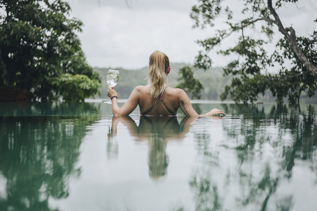 A girl with blonde hair in a swimsuit holding a glass of champagne looking out into a lake from a swimming pool.