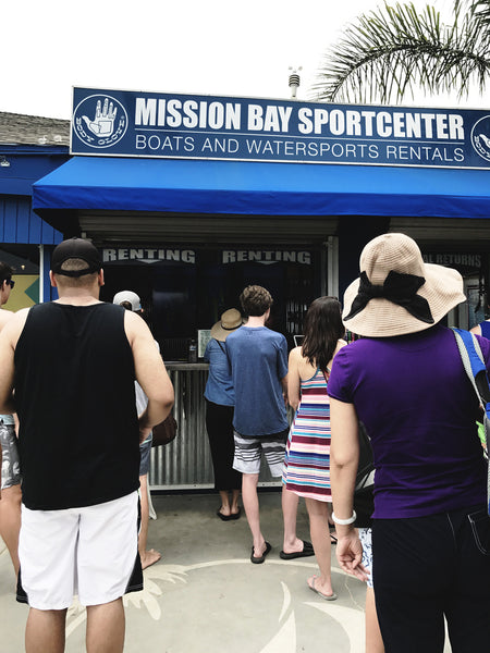 A photo of Mission Bay Sportscenter from the view of someone waiting in line for a paddle board rental