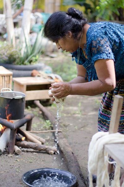 Long-term artisan partner Rosa wrings water out of fabric for dying, authentic naturally died products, Guatemala ethical fashion, maya weavers