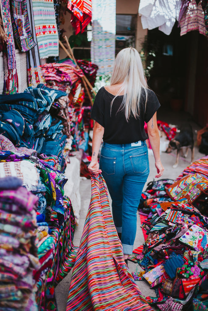 Hiptipico founder Alyssa Yamamoto walks through vibrant Guatemalan market searching for textiles wearing ethically made MUD jeans, ethical fashion bloggers, best ethical fashion options in the US, how to shop for clothes ethically
