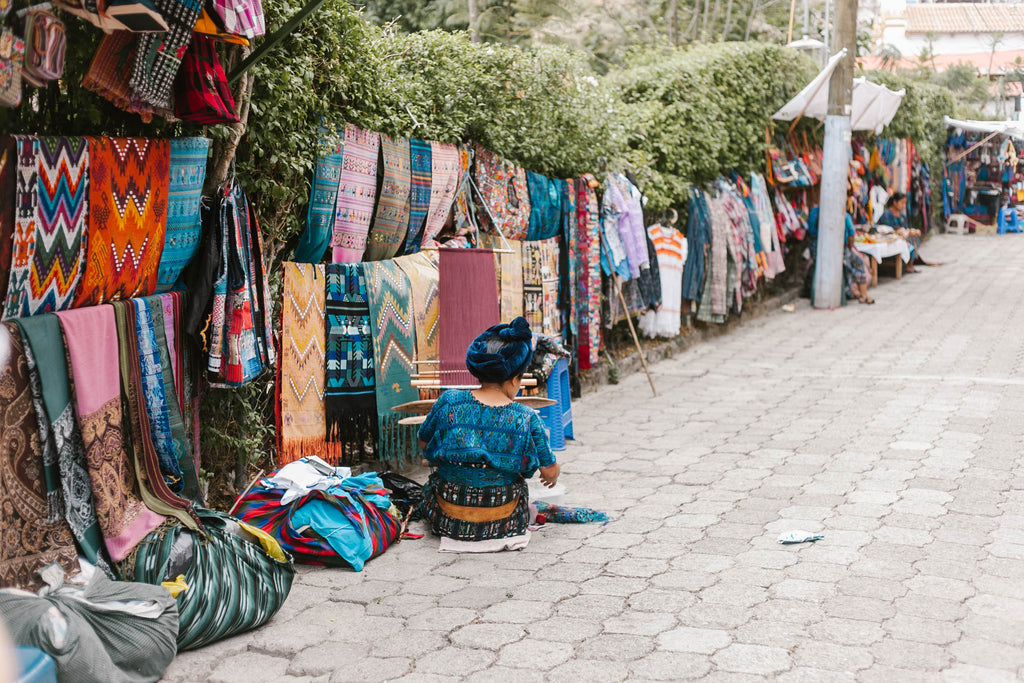 Artisan in traditional blue corte sits at stall on market street, hiptipico, travel blogs, ethical travel blogger, best travel blogs, travel guatemala, Santa Catarina guatemala, what to do in Santa Catarina Guatemala, Guatemala destinations
