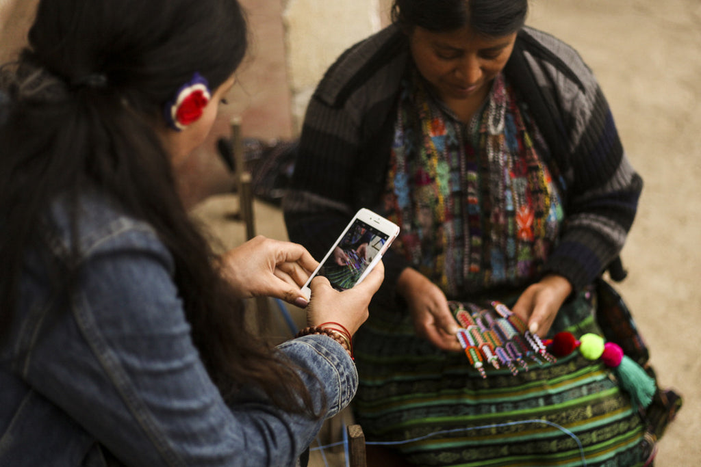 Tour participant takes picture of weaving process on her iphone, most enjoyable travel experiences Guatemala, cultural immersion opportunities