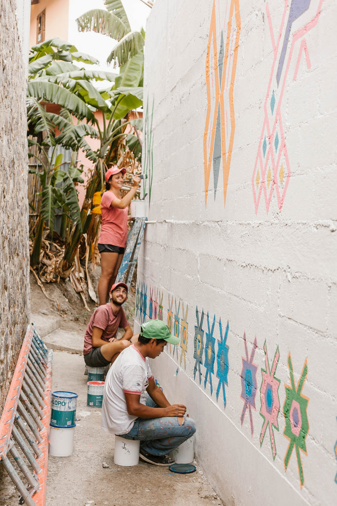 Painters in Santa Catarina alley working as part of the Pintando Santa Catarina Palopó with white wall and traditional designs, ethical travel options, cool things to see on Lake Atitlan, must visit towns Lake Atitlan