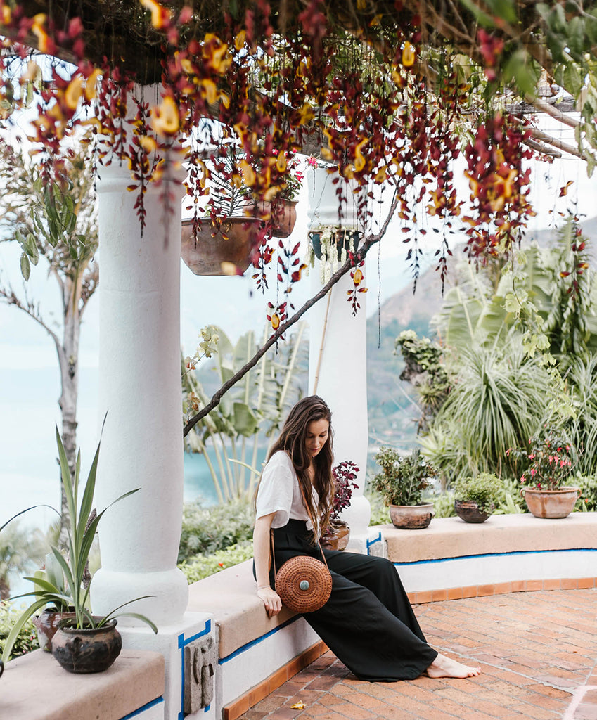 She Is Not Lost Blogger Carina Otero sits thoughtfully with Hiptipico Crossbody Bag at lookout under expanse of red and yellow hanging flowers, ethical travel bloggers, best resorts in Guatemala, where should I stay in Guatemala