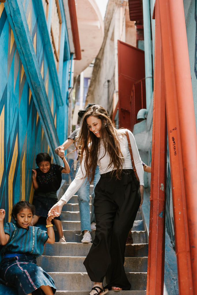 Carina Otero and Alyssa Yamamoto with local children in colorful stairway in Santa Catarina Palopó, travel bloggers, social impact bloggers, ethical travel blogs, top blogs about ethical travel, ethical travel in Guatemala, ethically travel to Lake Atitlan region