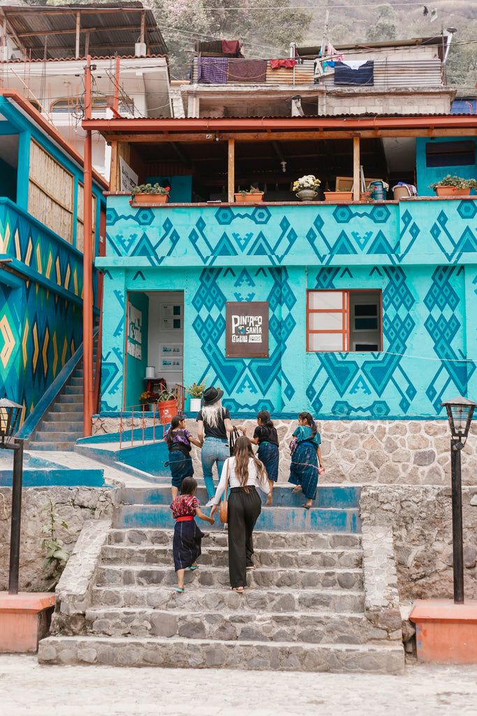 Hiptipico founder Alyssa, She Is Not Lost blogger Carina, and local kids walk up steps through blue-green town square towards tienda and artisan workshop, ethical travel blogs, ethical travel bloggers, where to go in Santa Catarina