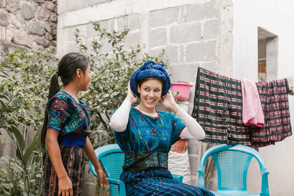 She Is Not Lost blogger Carina otero smiles as she feels the large blue headwrap traditionally worn in Santa Catarina Palopó, best experiences in Guatemala, crazy things to do in Guatemala, travel ethically in guatemala, ethical travel blogs, ethical travel bloggers