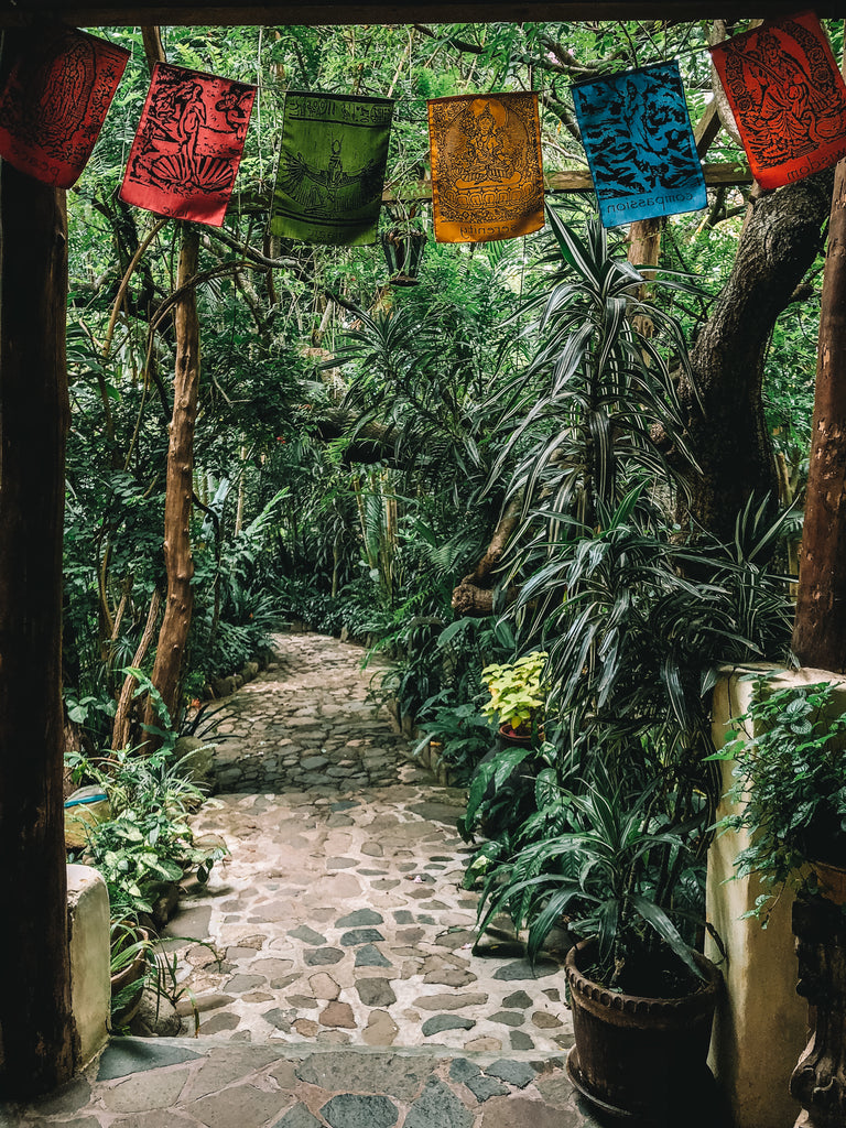 A brick pathway leads through lush wooded area with small cloth flags with spiritual figures at the top of the doorway, san marcos yoga, san marcos lake atitlan, san marcos sauna, where to do yoga by the lake, where to do yoga in Lake Atitlan, Lake Atitlan travel destinations, travel ethically in Lake Atitlan.