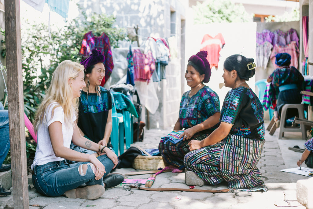 Hiptipico founder Alyssa laughs with 3 Artisan Partners dressed in traditional blue corte in home workshop, social impact fashion companies, ethical fashion brands in Guatemala, best B-Corp certified brands