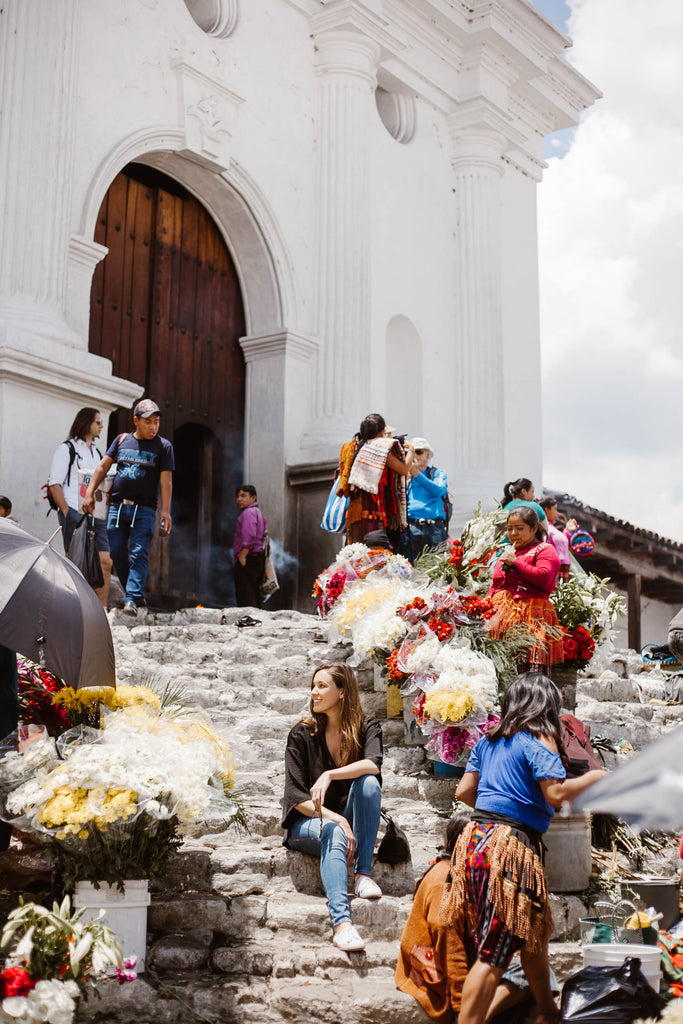 She Is Not Lost blogger Carina Otero sits smiling on Chichicastenango church steps surrounded by yellow, white and red bunches of flowers and vendors, Chichicastenango travel, Places to visit in Guatemala, must see guatemala travel, ethical travel in Guatemala, textile sourcing locations Central America