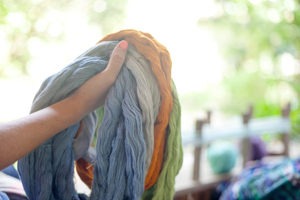 Model holds assorted bundles of dyed fabric in orange, blue, and grey strands, maya weaving workshops, how to see maya weavers work, handcrafted textiles from Guatemala