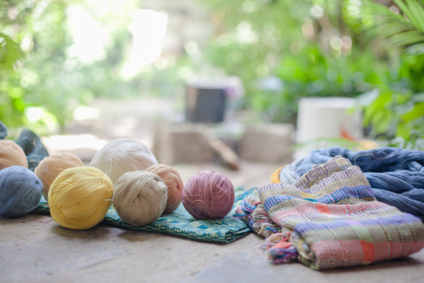 Balls of dyed fabric in assorted colors on top of table runners and textiles on table, authentic naturally dyed products, ethically produced textiles from Guatemala, ethical fashion blogs