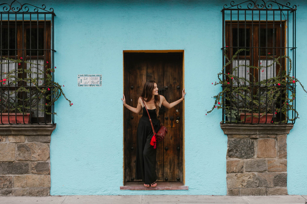 Carina Otero poses in doorway of blue building with red flowers, Antigua Guatemala Travel, Ethical Travel Options in Guatemala, Best Destinations in Antigua