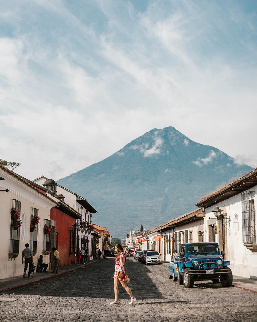 She Is Not Lost blogger Carina Otero walks thoughtfully on brick road in Antigua Guatemala with volcano in the horizon, volcano travel destinations, tropical travel destinations, best central american travel locations, blogs about central america, guatemala travel blog, ethical travel companies