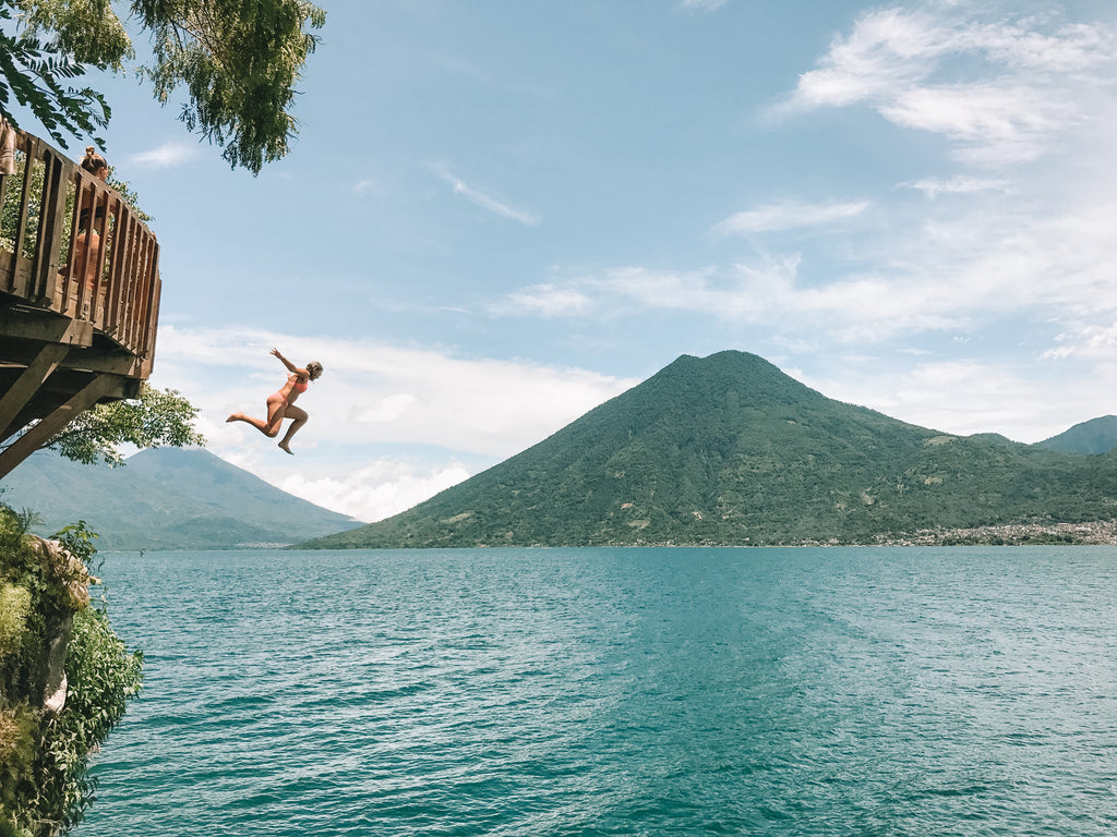 Hiptipico employee in peach suit jumps off sturdy wood platform into Lake AtitlanHiptipico ethical travel, where to go on Lake Atitlan, best swimming spots, cliff jumping Lake Atitlan, diving Lake Atitlan, best diving spots in Lake Atitlan, must do in Guatemala