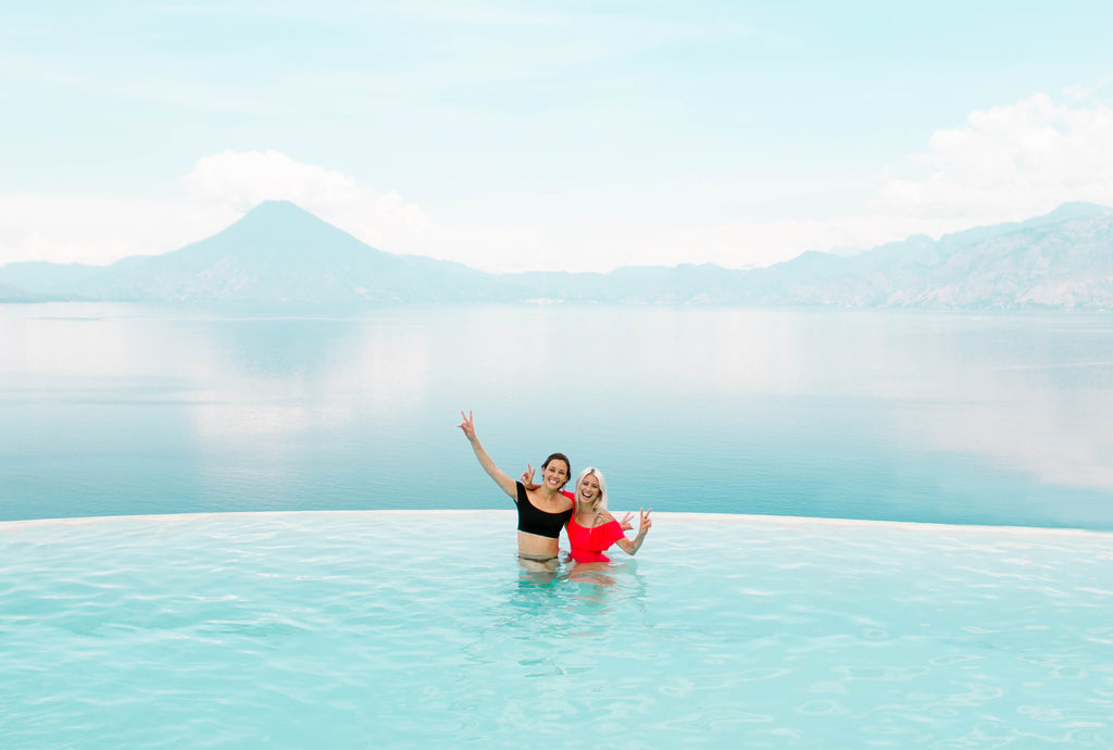 She Is Not Lost blogger Carina Otero and Hiptipico founder Alyssa Yamamoto pose with peace sign at Tzampoc resort pool overlooking Lake Atitlan, She Is Not Lost Travel, Travel Blogs, Ethical Travel Bloggers, Sustainable Travel, How To Travel Ethically, Guatemala Ethical Brands