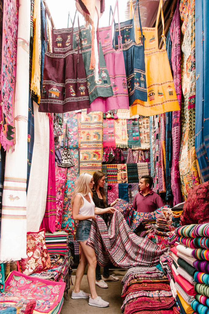 Hiptipico founder Alyssa and She Is Not Lost blogger Carina work with artisan to source textiles in colorful Chichicastenango market stall, ethically sourced textiles, ethical fashion in Guatemala, sourcing ethically in Guatemala