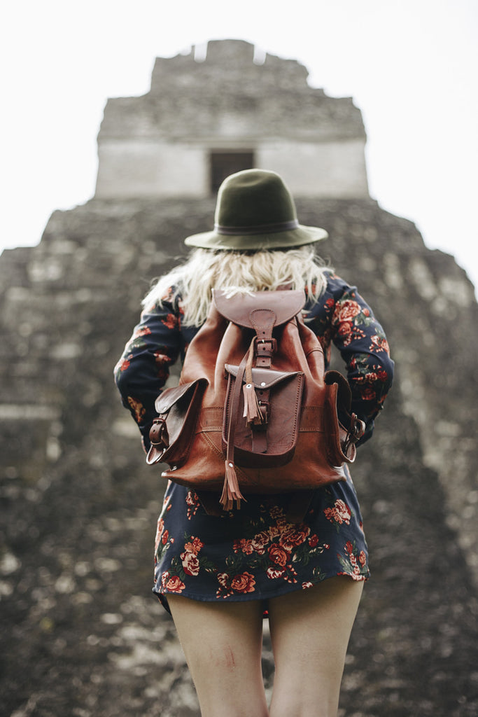 A photo of Alyssa getting ready to hike up some of the ruins and wearing a green wide brim hat, a leather backpack, and a floral mini dress.