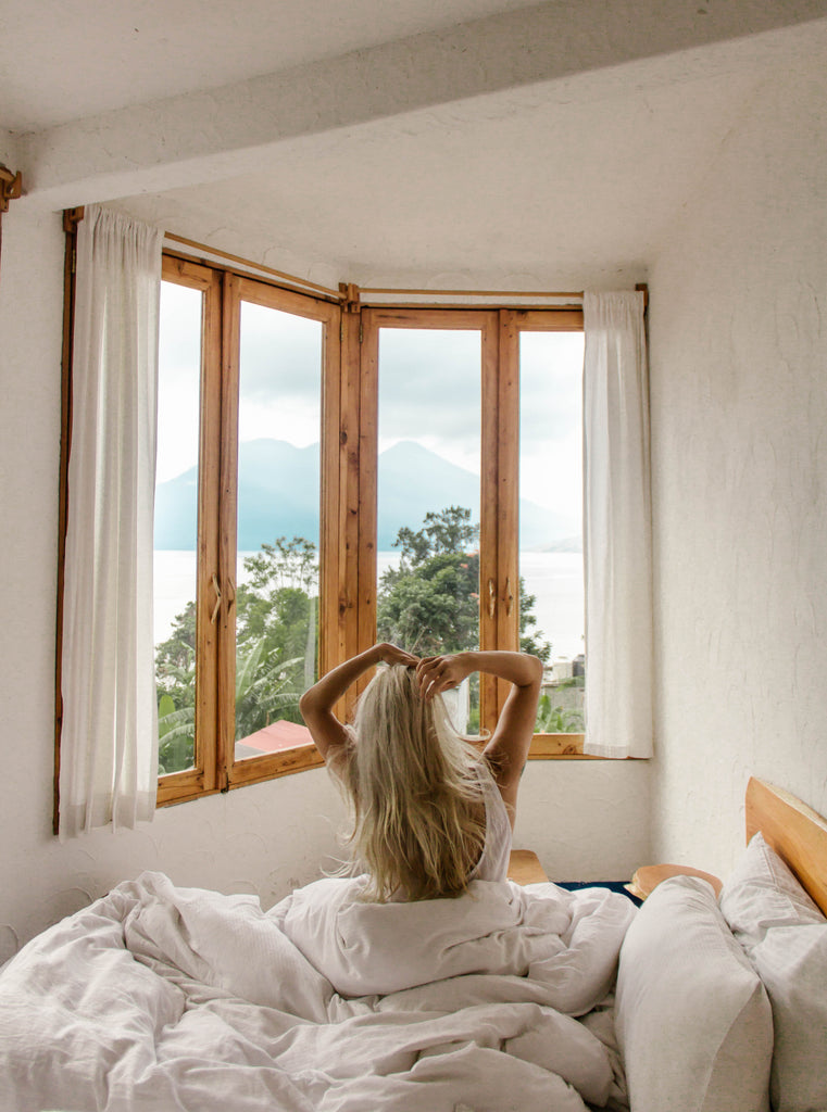 Hiptipico founder Alyssa looks out window in her room at Lush Atitlan ecohotel from bed with fluffy white sheets and pillows, ecohotels in Guatemala, ecofriendly lodging in Guatemala, ecofriendly resorts in Lake Atitlan, where to stay in San Marcos, San Marcos hotels