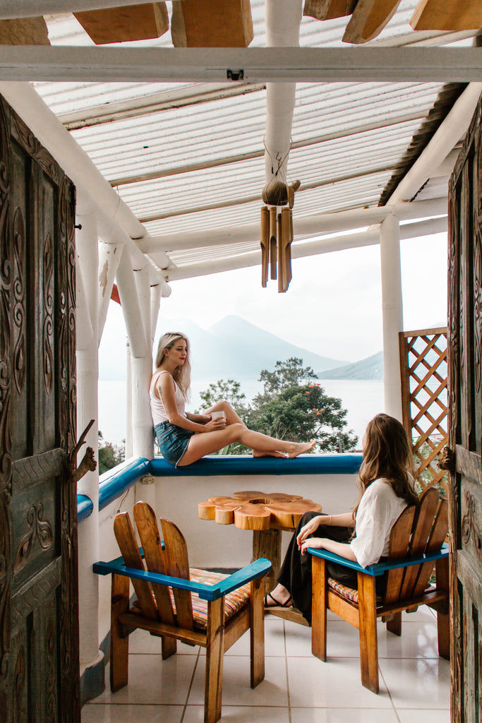 Hiptipico founder Alyssa seated on ledge of room overlooking Lake Atitlan and its volcanoes with She Is Not Lost Blogger Carina Otero in Lush Atitlan hotel, Lush Atitlan guatemala, Guatemala hotels, coolest places to stay Guatemala, best places to stay on Lake Atitlan, ethical travel in Lake Atitlan
