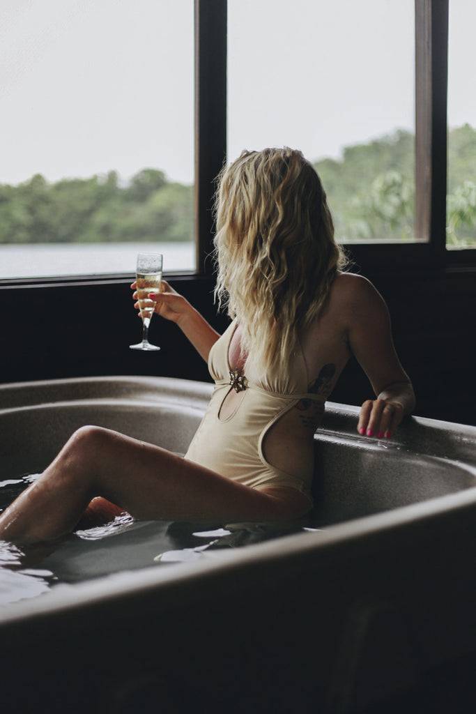 A blonde haired girl in a one piece swimsuit sitting in a hot tub and looking out the window of the hotel at a lake outside